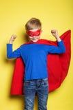 Chłopiec w czerwonym super bohatera przylądku i masce nadczłowiek Pracowniany portret nad żółtym tłem Obraz Royalty Free