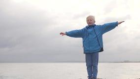 Chłopiec w deszczowa stojakach przeciw niebu i prostuje jego ręki zbiory
