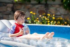 Chłopiec w dużym pływackim basenie, pije sok w gorącym summe Fotografia Royalty Free