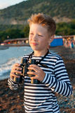 Chłopiec w garnizonowej nakrętce z i paskująca kamizelki pozycja blisko morza fotografia royalty free