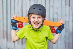 Chłopiec w hełmie pozuje z deskorolka Zdjęcia Royalty Free
