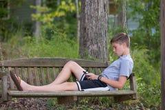 Chłopiec w huśtawce bawić się lub texting na telefonie Zdjęcia Royalty Free