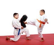 Chłopiec w kimonie uderza stopę kopnięcie symulant który w rękach inny sportowiec Zdjęcie Stock