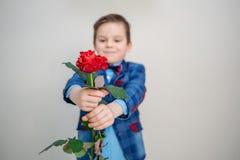 Chłopiec w kostium pozycji z czerwieni różą, odizolowywającą na lekkim tle zdjęcia royalty free