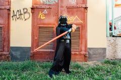 Chłopiec w kostiumu Darth Vader z kordzikiem Zdjęcia Stock