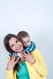 Chłopiec w koszulowym obsiadaniu z mamą na lekkim tle zdjęcie royalty free