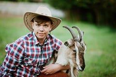 Chłopiec w kowbojskiej odzieży żywieniowej kózce z marchewką w gospodarstwie rolnym Zdjęcie Stock