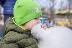 Chłopiec w kurtce je bawełnianego cukierek na ulicie Obraz Royalty Free
