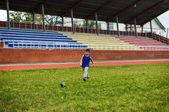 Chłopiec w mundurze bawić się futbol przy stadium obrazy royalty free