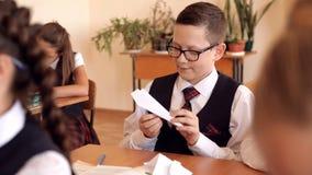 Chłopiec w mundurze przy szkołą w sali lekcyjnej robi papierowemu samolotowi zbiory wideo