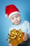 Chłopiec w nakrętce Święty Mikołaj z prezentami obraz stock