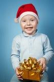 Chłopiec w nakrętce Święty Mikołaj z prezentami fotografia stock