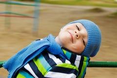 Chłopiec w nakrętki i szalika jazdie na carousel Obraz Royalty Free