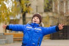 Chłopiec w niebieskiej marynarce rozprzestrzenia jego ręki Fotografia Royalty Free