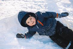 Chłopiec w niebieskiej marynarki sztuce z śniegiem, zima wakacje Zdjęcia Stock