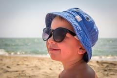 Chłopiec w okularach przeciwsłonecznych na plaży Zdjęcia Royalty Free