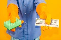 Chłopiec w płuczkowych rękawiczkach trzyma paczkę dolary w jeden ręce i gąbce w inny Pojęcie pranie brudnych pieniędzy i podatek fotografia stock