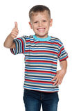 Chłopiec w pasiastej koszula trzyma jego kciuk up fotografia stock
