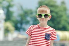 Chłopiec w pasiastej koszulce i szkło stojaki przeciw backgrou Zdjęcia Stock