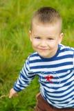 Chłopiec w pasiastej koszulce pozuje na trawie w ogródzie zdjęcie royalty free