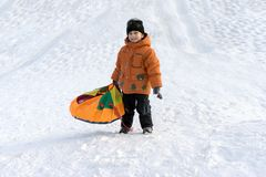Chłopiec w pomarańczowej kurtce i czarnym kapeluszu na Pogodnym zima dniu z śnieżnym obruszeniem na specjalnej babeczce i śmiecha fotografia royalty free