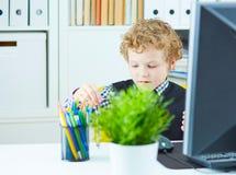 Chłopiec w postaci urzędnika bawić się z dividers Fotografia Stock