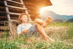 Chłopiec w słomianym kapeluszu kłama w sianie blisko stajni Obraz Stock