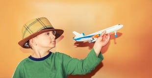 Chłopiec w słomianym kapeluszu trzyma samolot pasażerskiego pojęcie wolność i podróż, obraz royalty free