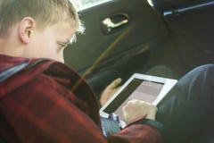 Chłopiec w samochodzie bawić się na pastylka komputerze osobistym obrazy royalty free