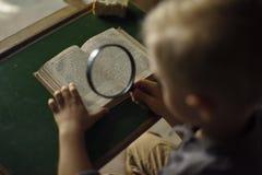 Chłopiec w starym domowym czytaniu tajemnicza książka zdjęcie royalty free