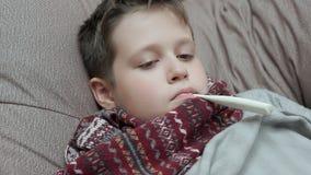 Chłopiec w szaliku miary domowa temperatura He dostawać zimno zbiory wideo