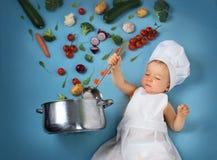 Chłopiec w szefa kuchni kapeluszu z kulinarną niecką i warzywami Obrazy Royalty Free