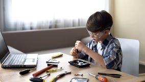 Chłopiec w szkła działaniu na szkolnym projekcie, attentively odplata peceta szczegół zdjęcia royalty free