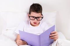 Chłopiec w szkłach czyta książkę w łóżku obraz stock