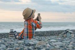 Chłopiec w szkocka krata kapeluszu i koszula siedzi na plaży i bierze obrazki na smartphone na tle morza i nieba Zdjęcia Royalty Free