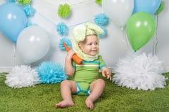 Chłopiec w wakacyjnym Wielkanocnego królika królika kostiumu z wielkimi ucho, ubierającymi w zieleni ubrań onesie, siedzi na dywa Obraz Stock