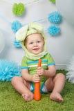 Chłopiec w wakacyjnym Wielkanocnego królika królika kostiumu z wielkimi ucho, ubierającymi w zieleni ubrań onesie, siedzi na dywa Fotografia Royalty Free