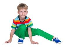Chłopiec w zielonych spodniach siedzi obrazy royalty free