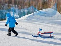 Chłopiec w zimie niesie śnieżną hulajnogę ciężką na czystym białym śniegu zdjęcie royalty free