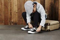 Chłopiec wiąże shoelace na skrzynce Obraz Stock