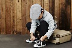 Chłopiec wiąże shoelace na skrzynce Zdjęcia Royalty Free