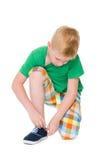 Chłopiec wiąże shoelaces obraz stock