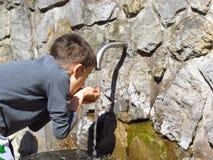 Chłopiec woda pitna przy wiosną zdjęcia stock