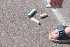 Chłopiec wp8lywy kreda od asfaltu zakończenie ręka zdjęcia stock