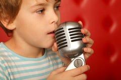 chłopiec wręcza mikrofonu jego portret fotografia royalty free