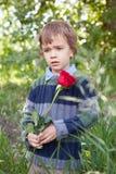 chłopiec wręcza smutnej czerwieni małej parkowej róży jej mieniu zdjęcie stock