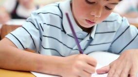 Chłopiec writing na jego notatniku zdjęcie wideo