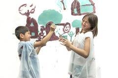 Chłopiec wskazuje paintbrush przy siostrą Zdjęcia Stock