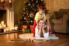 Chłopiec wspina się jego łgarskiego mamy ` s plecy zdjęcia stock