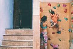 Chłopiec wspina się na dziecka ` s pięcia ścianie obrazy royalty free